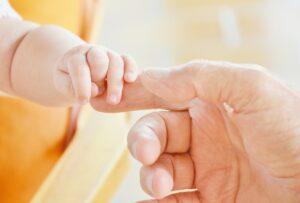 baby holding mum's hand