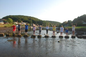 young people standing on stones across the river in Lerryn