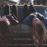 two girls lying on a car and chatting