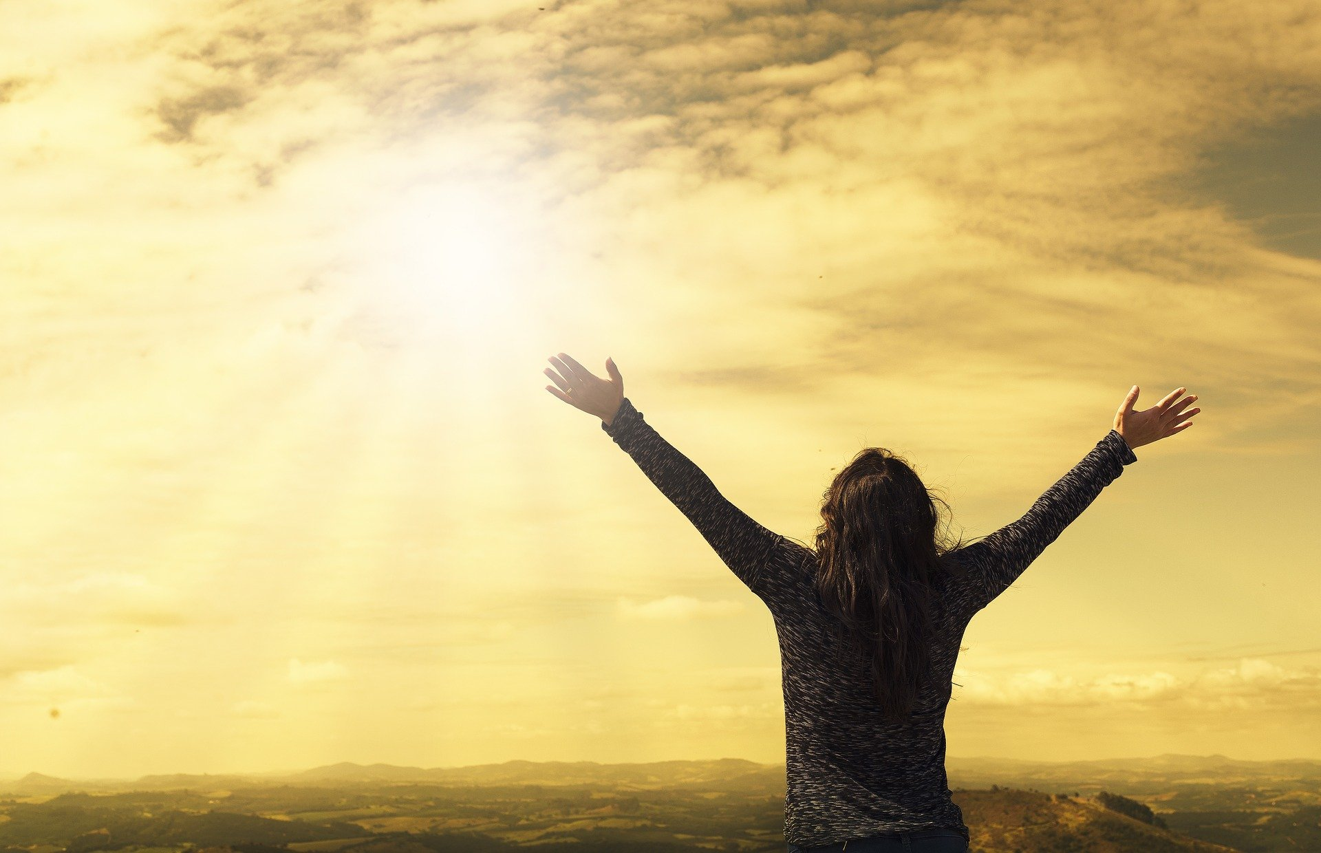 Praying with arms outstretched