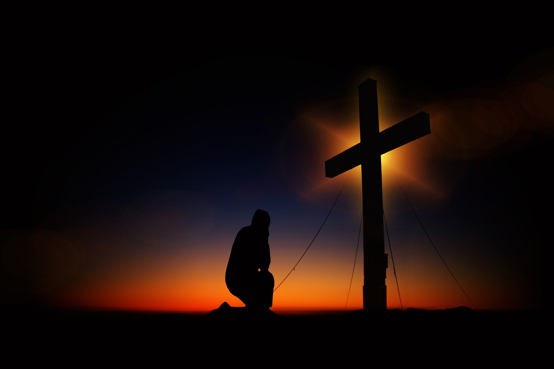 Kneeling humbly before the Cross