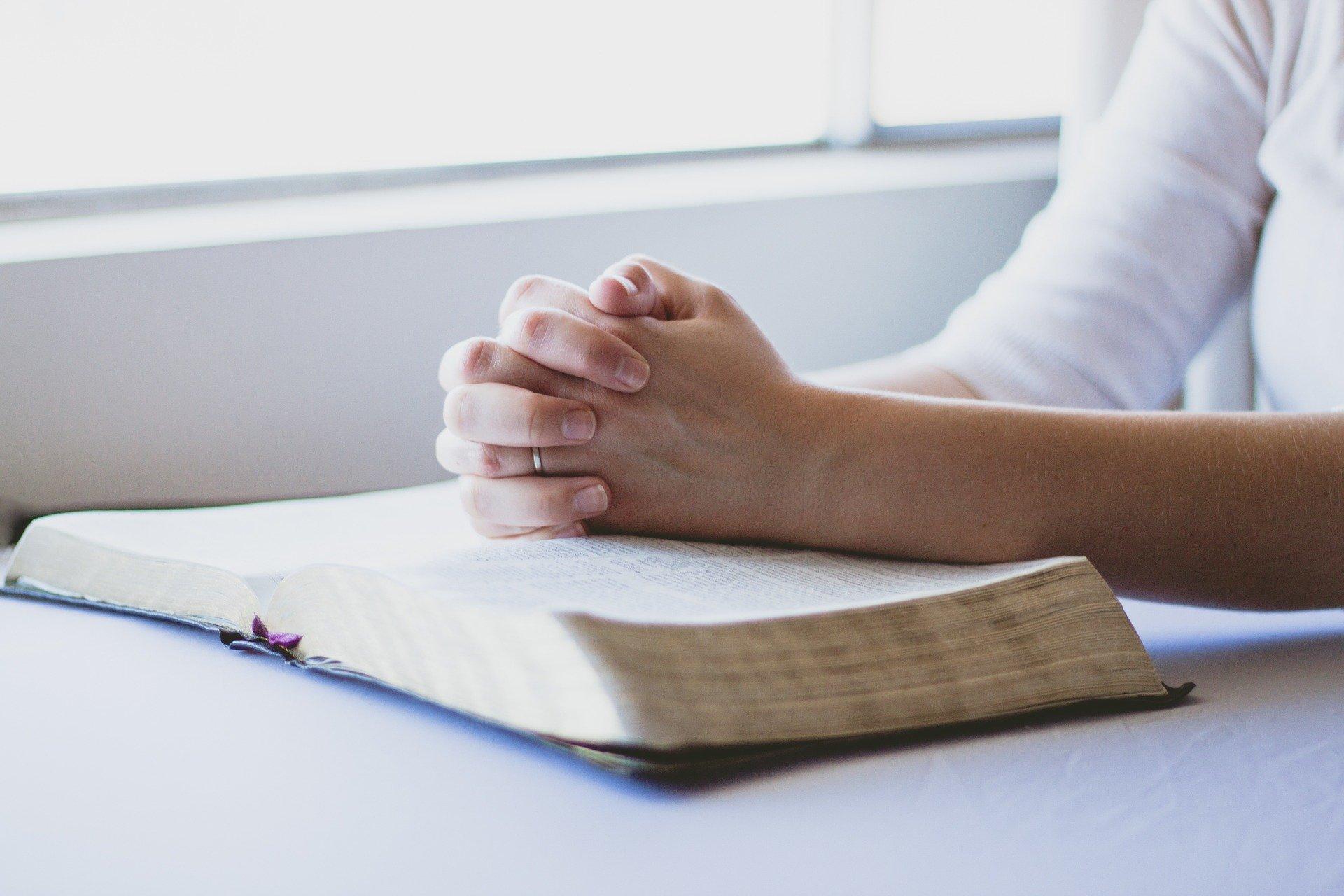 man praying over the Bible
